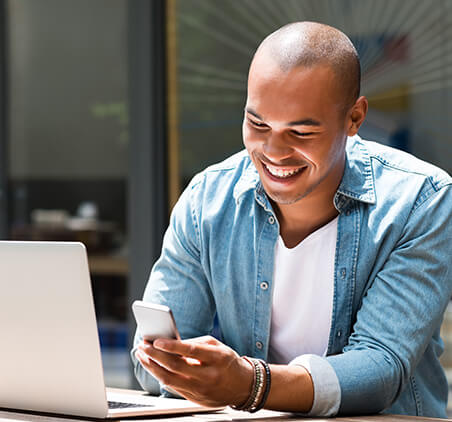 smiling man looking at phone while on computer