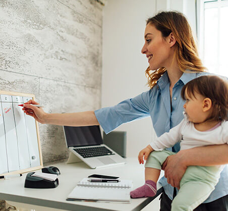 woman with baby writing on calendar
