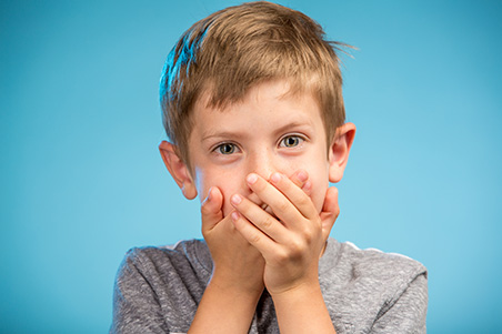 young boy covering his mouth