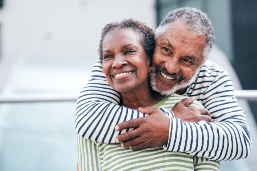 Smiling older black couple with the man standing behind the woman and giving her a hug