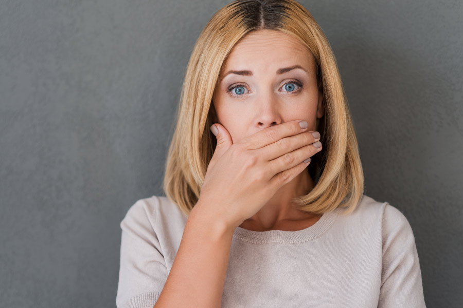 Blonde woman covers her mouth due to fear of halitosis or bad breath.